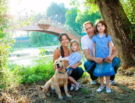 Happy family father mother kids and dog outdoor river park
