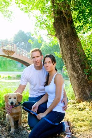 mujer perro: feliz pareja posando con el perro retirever de oro en parque al aire libre