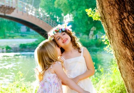 entre filles: filles enfant jouant au printemps en plein air du fleuve oreille chuchoter parc Banque d'images