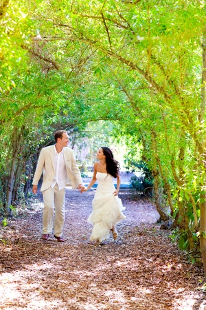couple just married happy running in green park outdoor Stock Photo
