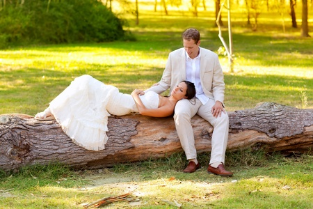 woman lying on husband leg in a park trunk just married