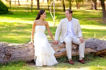 mediterranean forest: couple happy in love in outdoor park sitting in tree trunk Stock Photo