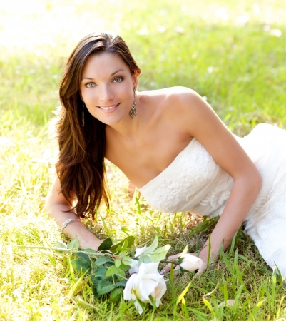 bride woman lying in park grass with white rose photo