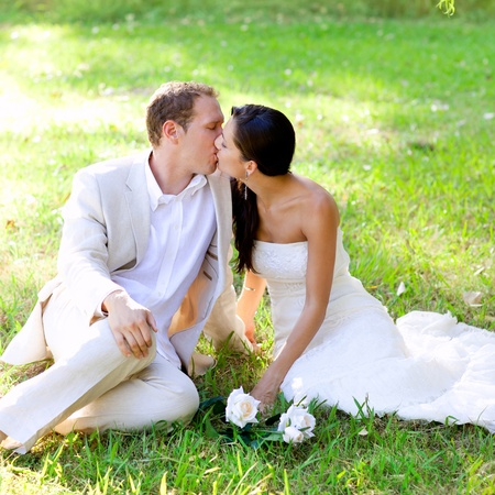 couple happy in love kissing sitting in park green grass photo