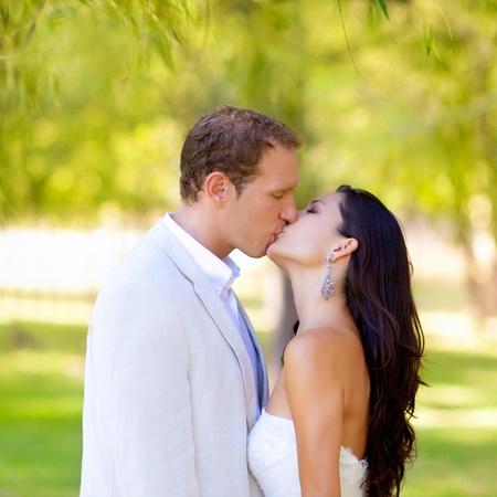 enamorados besandose: pareja feliz en el amor besos en el parque bajo los árboles Foto de archivo
