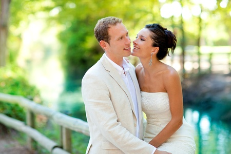 marriage ceremonies: couple of lovers in love in park river outdoors hug