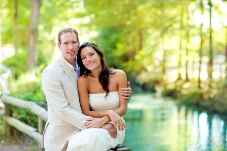 marriage ceremony: couple of lovers in love in park river outdoors hug
