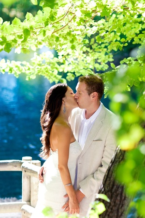 young couple kissing: couple in love kissing in forest tree blue lake outdoors