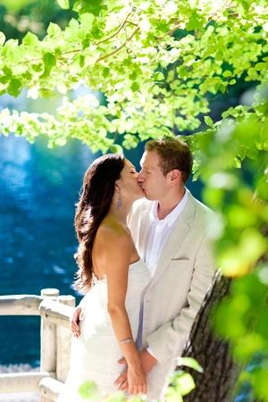 hombres besandose: pareja de enamorados bes�ndose al aire libre en el bosque de �rboles lago azul Foto de archivo