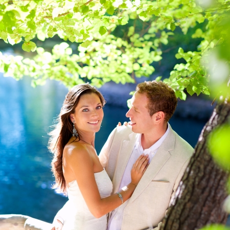 wedding portrait: couple in love hug in forest tree blue lake outdoors
