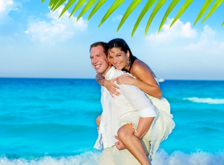 couple in love piggyback playing in a beach at blue Mediterranean
