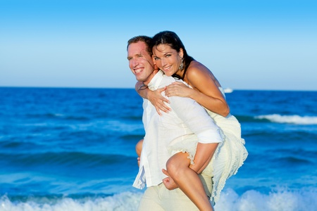 couple in love piggyback playing in a beach at blue Mediterranean photo