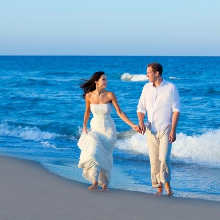 beach wedding: Mediterranean couple walking in blue beach shore