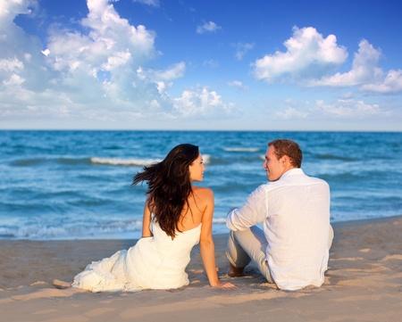 pareja de esposos: pareja de enamorados sentados en la playa azul en viajes de vacaciones