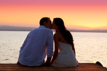 couple kissing at sunset sitting in jetty at orange sea lake photo