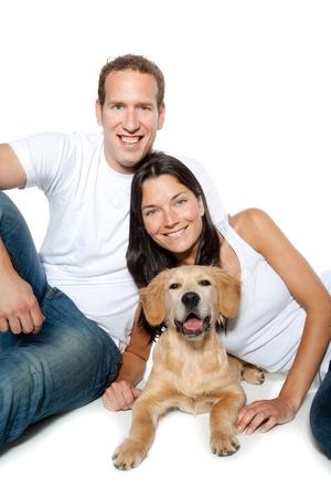 puppy love: pareja en el amor con un perro golden retriever aislados en blanco