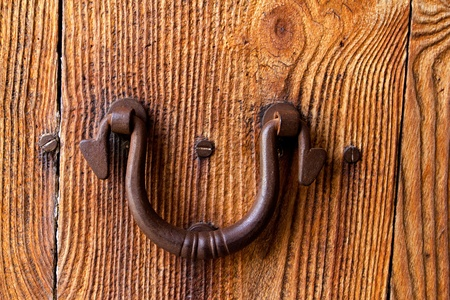 door bolt: Ibiza traditional rusted iron door handle on weathered wood Stock Photo