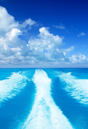 Boat wake prop wash on turquoise sea in sunny day photo