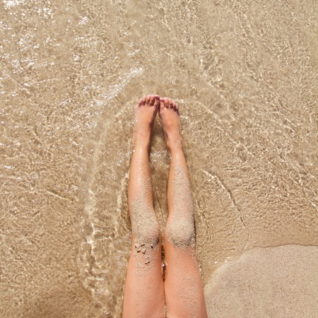 Children girl legs in beach sand shore at summer vacation photo