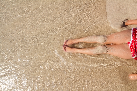 sandy feet: Children girl legs in beach sand shore at summer vacation Stock Photo