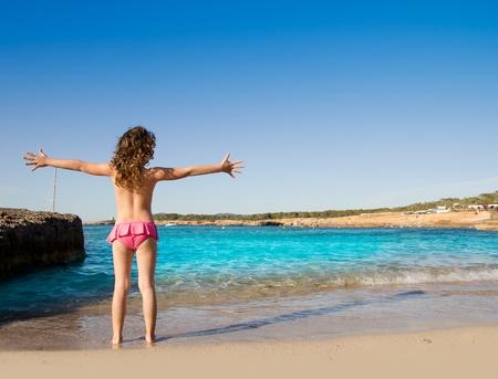 Ibiza Cala Conta beach open arms little girl happy in summer vacation photo