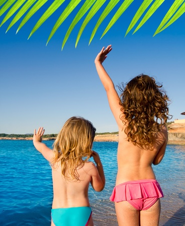 Ibiza Cala Conta beach little girls greeting hand sign saying bye Stock Photo
