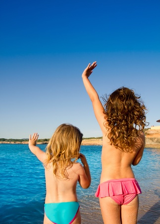 rear views: Ibiza Cala Conta beach little girls greeting hand sign saying bye Stock Photo