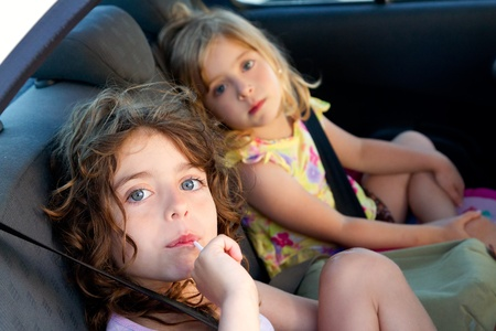vehicle seat: little girls inside car eating candy stick selective focus Stock Photo