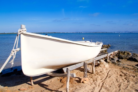 beached: beached boat in Formentera Estany des Peix with La Savina in background