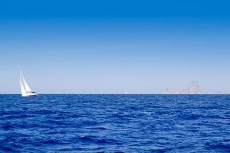 sea sports: Ibiza Es Vedra and sailboat in blue mediterranean sea