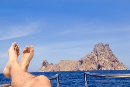 boat party: Ibiza relaxed Es Vedra boat bow view with crossed man legs and feet