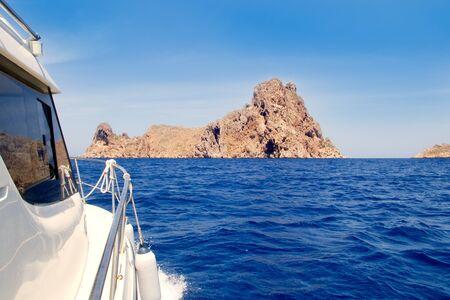Ibiza yacht reaching Es Vedra island in Mediterranean blue sea photo