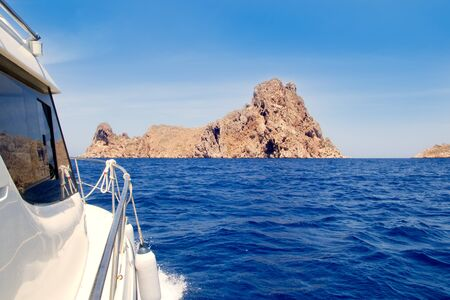 Ibiza yacht reaching Es Vedra island in Mediterranean blue sea photo
