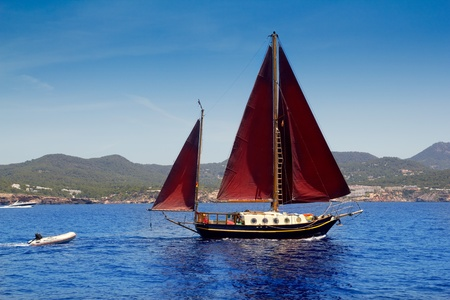 ibiza: Ibiza Red sails sailboat in Sa Talaia coast of Balearic Islands Stock Photo