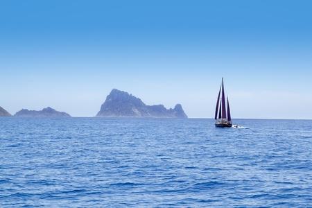es: Ibiza Red sails sailboat in Es Vedra at blue mediterranean sea of Balearic