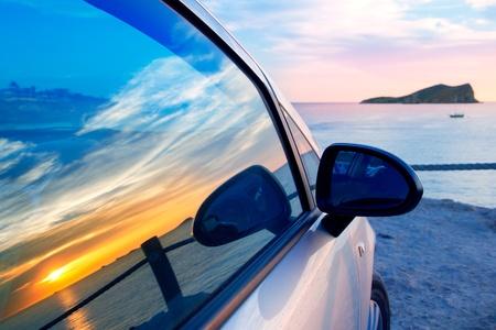 beaches of spain: Ibiza cala Conta Conmte susnset reflection y car window glass Stock Photo