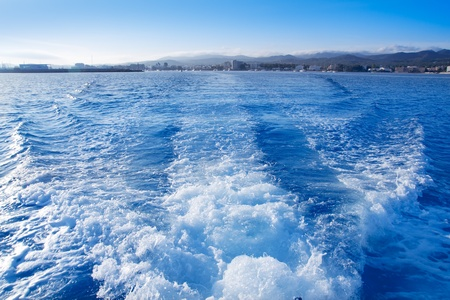 Ibiza San Antonio Abad from boat wake in blue mediterranean photo