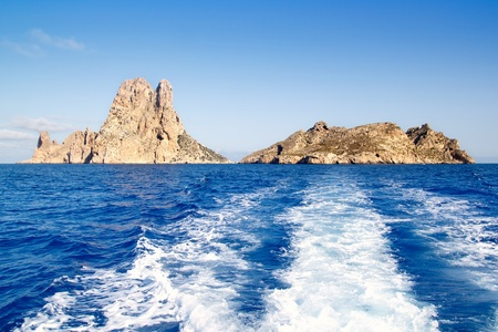Es Vedra islet and Vedranell islands in blue Mediterranean boat wake photo