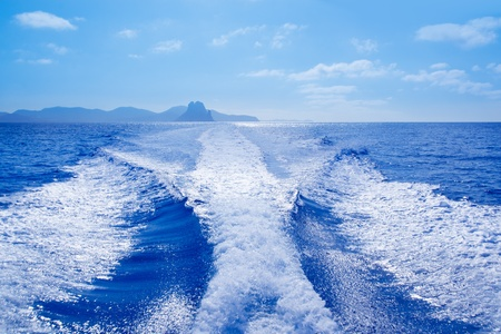 seaway: Es Vedra islet and Vedranell islands with boat wake in mediterranean Spain Stock Photo