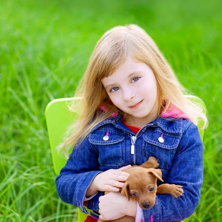 blonde yeux bleus: Kid fille blonde avec des chiots de compagnie chien de s'asseoir dans l'herbe verte en plein air