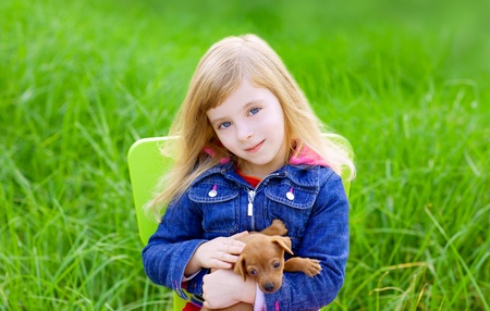 Blond kid girl with puppy pet dog sit in outdoor green grass Stock Photo - 11268688
