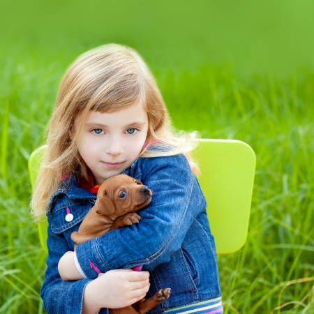 Blond kid girl with puppy pet dog sit in outdoor green grass photo
