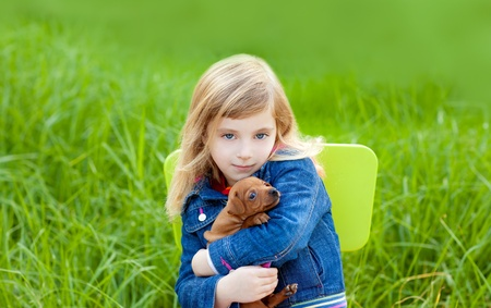 Blond kid girl with puppy pet dog sit in outdoor green grass Stock Photo - 11268687