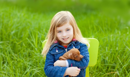 Blond kid girl with puppy pet dog sit in outdoor green grass Stock Photo - 11268686