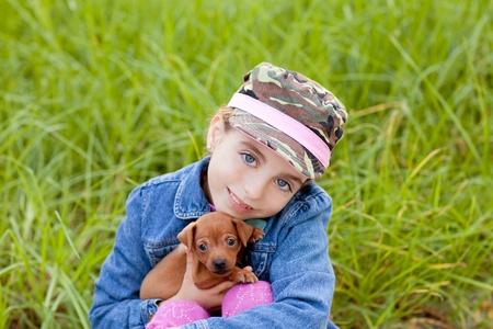 little girl with pet puppy mascot mini pinscher in outdoor green grass photo