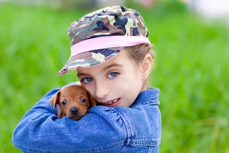 little girl with pet puppy mascot mini pinscher in outdoor green grass photo