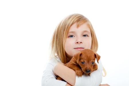 ni�os rubios: Los ni�os chica rubia con cachorro de perro mascota de pinscher mini-sobre fondo blanco