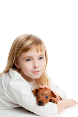 blond kid girl with mini pinscher pet mascot dog on white background photo