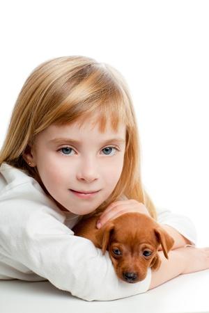 blond kid girl with mini pinscher pet mascot dog on white background photo