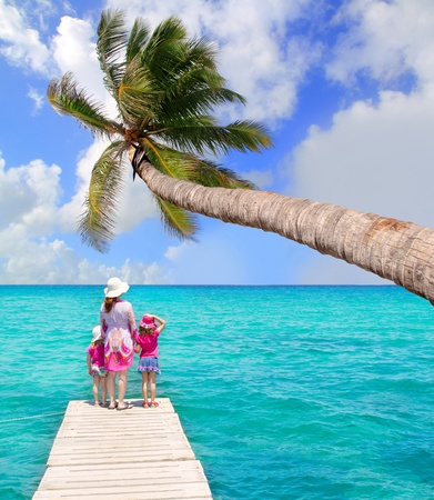 playas tropicales: Hijas y la madre en el embarcadero en Formentera con el turquesa del mar Foto de archivo